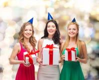 Femmes de sourire dans des chapeaux de partie avec des boîte-cadeau Image stock