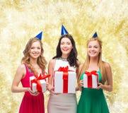 Femmes de sourire dans des chapeaux de partie avec des boîte-cadeau Images stock