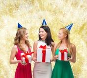Femmes de sourire dans des chapeaux de partie avec des boîte-cadeau Image libre de droits