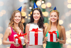 Femmes de sourire dans des chapeaux de partie avec des boîte-cadeau Photographie stock libre de droits