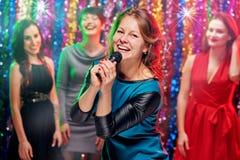 Femmes de sourire dans le karaoke Images libres de droits