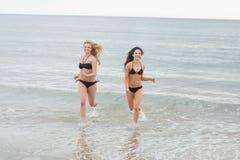 Femmes de sourire de bikini courant dans l'eau à la plage Photo stock