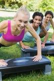 Femmes de sourire faisant l'aérobic d'étape Image stock