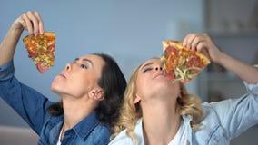 Femmes de sourire mangeant avidement de la pizza savoureuse, dépendance d'aliments de préparation rapide, régime malsain clips vidéos