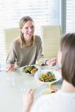 Femmes de sourire mangeant ensemble à la table Photographie stock libre de droits