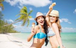 Femmes de sourire mangeant la crème glacée sur la plage Photographie stock libre de droits