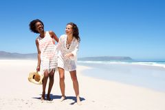 Femmes de sourire marchant ensemble au bord de la mer Photographie stock