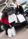 Femmes de sourire mettant des sacs à provisions dans le véhicule Images stock