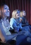 Femmes de sourire observant le film dans le théâtre Photos stock