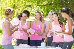Femmes de sourire organisant l'événement pour la conscience de cancer du sein Photographie stock libre de droits