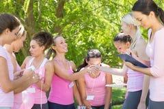 Femmes de sourire organisant l'événement pour la conscience de cancer du sein Photos libres de droits