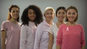 Femmes de sourire portant les vêtements et les rubans roses, signe de conscience de cancer du sein banque de vidéos