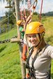 Femme avec le casque souriant en parc d'aventure Images stock