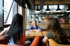 Femmes de sourire s'asseyant au café de café, de sourire et de boissons confortable Image stock