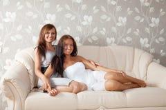 Femmes de sourire s'asseyant dans la salle de séjour Image stock