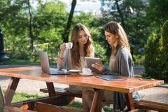 Femmes de sourire s'asseyant dehors en café potable de parc utilisant l'ordinateur portable Images stock