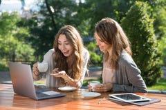 Femmes de sourire s'asseyant dehors en café potable de parc utilisant l'ordinateur portable Photo stock