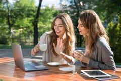 Femmes de sourire s'asseyant dehors en café potable de parc utilisant l'ordinateur portable Image libre de droits