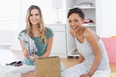 Femmes de sourire s'asseyant sur le plancher avec le panier Images stock