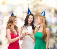 Femmes de sourire tenant des verres de vin mousseux Photographie stock libre de droits