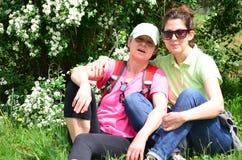 Femmes de touristes s'asseyant et étreignant extérieur Verticale de famille image libre de droits