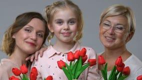 Femmes de trois générations tenant des tulipes, tradition de famille pour célébrer le 8 mars clips vidéos