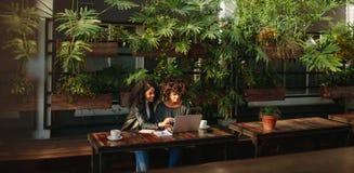 Femmes discutant le travail au-dessus du café Photographie stock