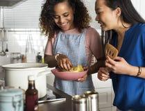 Femmes diverses faisant cuire dans la cuisine ensemble images libres de droits