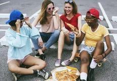 Femmes diverses s'asseyant sur le plancher mangeant de la pizza ensemble Images stock