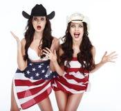 Femmes drôles dans des chapeaux enveloppés dans le drapeau des Etats-Unis Photos stock