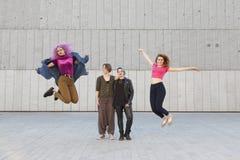 Femmes drôles sautant sur les vêtements colorés pour une photo de groupe Photo stock