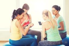 Femmes enceintes heureuses avec des instruments dans le gymnase Photographie stock libre de droits
