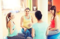 Femmes enceintes heureuses s'asseyant sur des boules dans le gymnase Photographie stock libre de droits