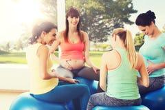 Femmes enceintes heureuses s'asseyant sur des boules dans le gymnase Image stock