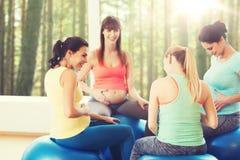 Femmes enceintes heureuses s'asseyant sur des boules dans le gymnase Images stock