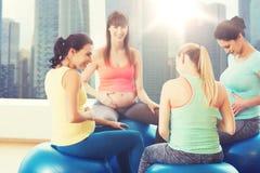Femmes enceintes heureuses s'asseyant sur des boules dans le gymnase Photos stock