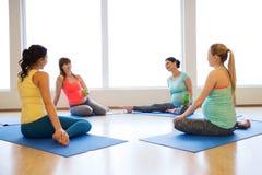 Femmes enceintes heureuses s'asseyant sur des tapis dans le gymnase Photo libre de droits
