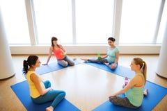 Femmes enceintes heureuses s'asseyant sur des tapis dans le gymnase Photographie stock