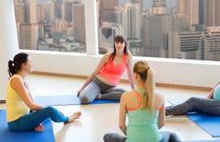 Femmes enceintes heureuses s'asseyant sur des tapis dans le gymnase Images stock
