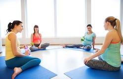 Femmes enceintes heureuses s'asseyant sur des tapis dans le gymnase Photos libres de droits