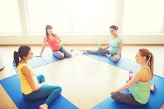 Femmes enceintes heureuses s'asseyant sur des tapis dans le gymnase Photo stock