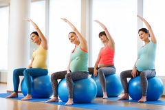 Femmes enceintes heureuses s'exerçant sur le fitball dans le gymnase Images stock