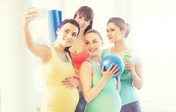 Femmes enceintes prenant le selfie par le smartphone dans le gymnase Photographie stock