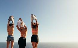 Femmes enlevant leurs dessus contre le paysage marin Image libre de droits