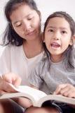 Femmes enseignant la fille ? lire un livre photo stock