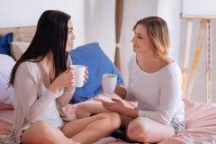 Femmes enthousiastes intéressées discutant quelque chose Photographie stock libre de droits