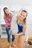 Femmes enthousiastes retenant un tapis dans la cuisine Photographie stock libre de droits