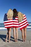 Femmes enveloppées dans les indicateurs américains sur une plage Image stock