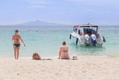 Femmes et amie détendant sur la plage et la mer tropicales Photographie stock