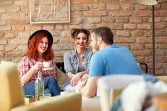 Femmes et homme parlant avec la tasse de café en café Images stock